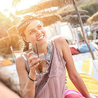 Young woman enjoys a beverage on the sand