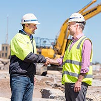 Staff from Renewal SA and McMahon Services shake hands on the site of Dock One