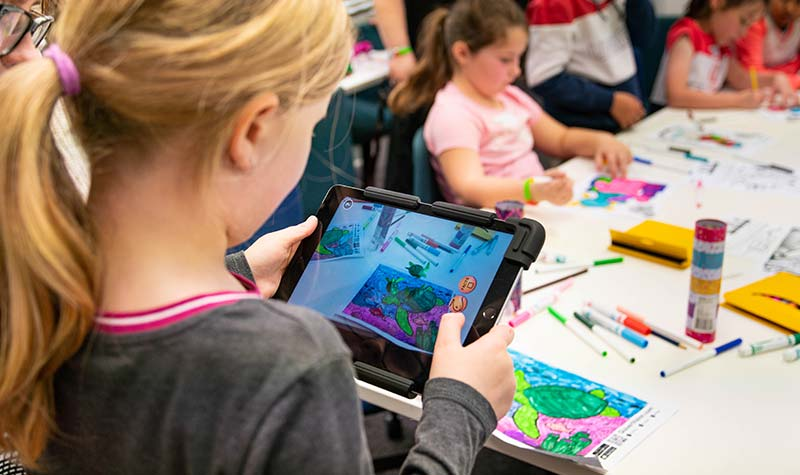 Students in awe at being able to transform their coloured-in pictures into 3D animations using an iPad and an augmented reality app.