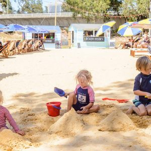 Three children play in the sand with buckets and spades