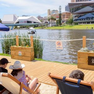 Urban Beach visitors enjoy riverbank views from the deck chairs