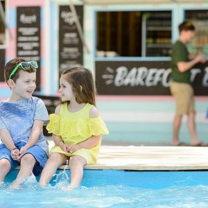 Two young children dip their feet in the paddle pool