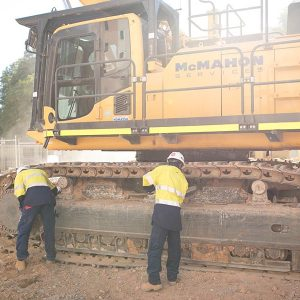 Alex and Dale remove debris from the tracks of an excavator