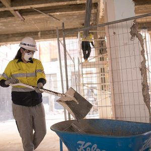 Jacinda, wearing a dust mask, uses a shovel and wheel barrow to help keep the site clean